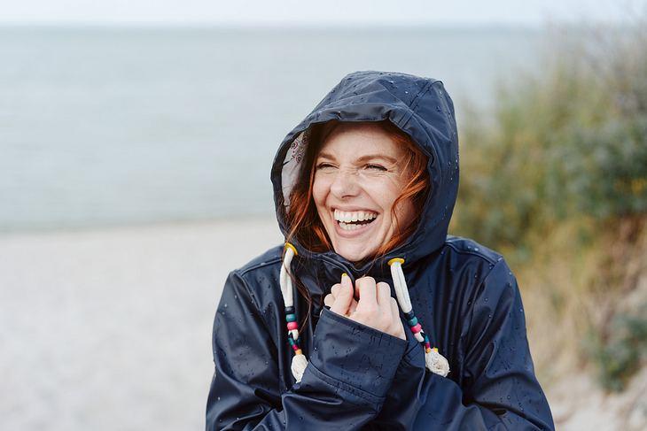 Frierende Frau im Mantel hält lachend die Kapuze fest