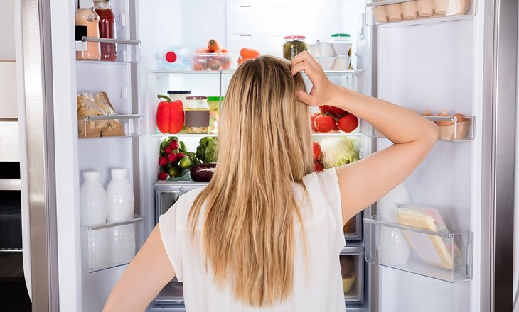 Frau steht fragend vor vollem Kühlschrank