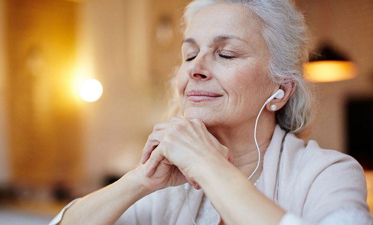 Ältere Frau hört mit Kopfhörern Musik