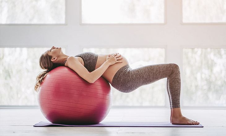 Schwangere rücklings auf Gymnastikball