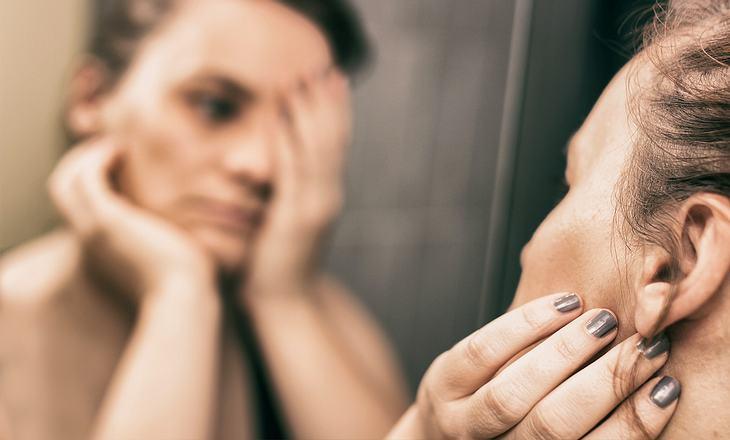 Frau mit Dysmorphophobie blickt in den Spiegel