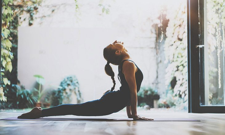 Frau macht Yogaübung Kobra
