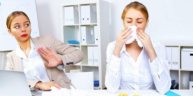 Frau niest im Büro