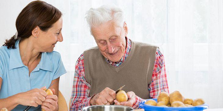 Frau hilft altem Mann beim Kochen