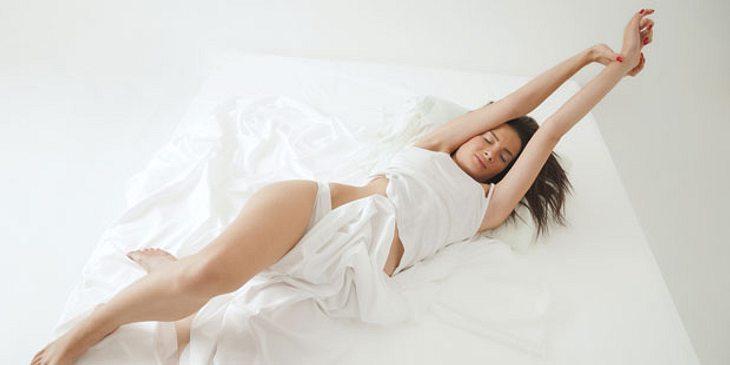 Frau räkelt sich im Bett