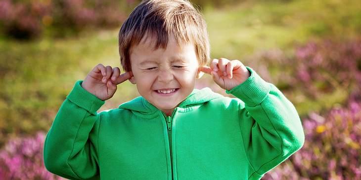 Kind hält sich Ohren zu