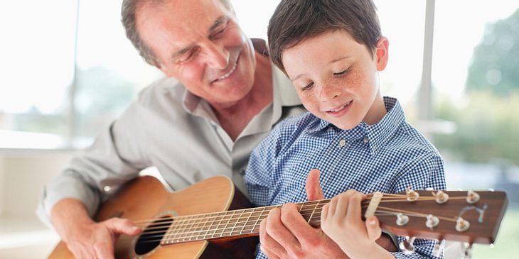 Opa spielt mit Enkel Gitarre