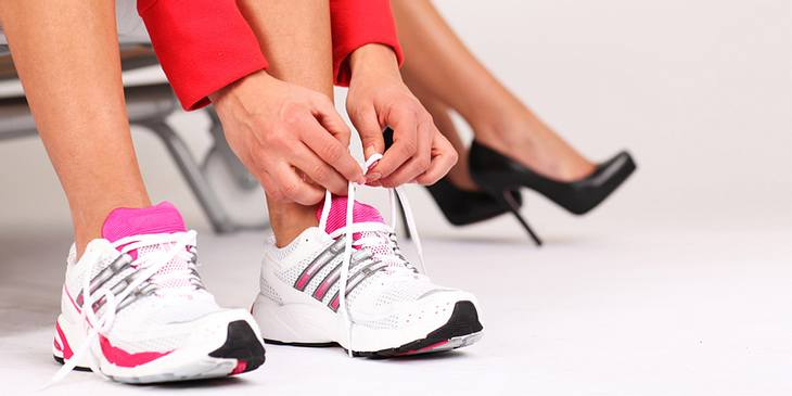 Frau bindet Schuhe zu