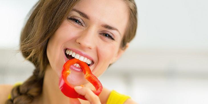 Frau isst Paprika