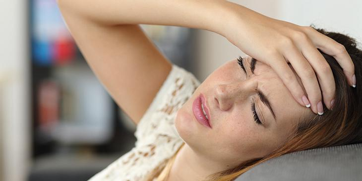 Frau mit Migräne auf Sofa