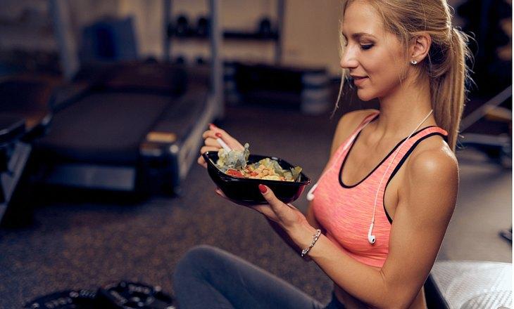 Sportliche Frau isst etwas