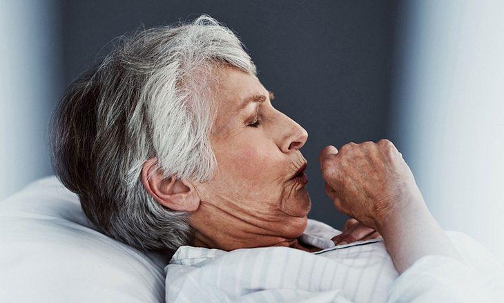 Ältere Frau mit Erkältung räuspert sich