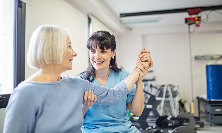 Frau hilft Seniorin bei der Haltung