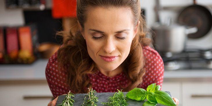 Eine Frau riecht an Kräutern