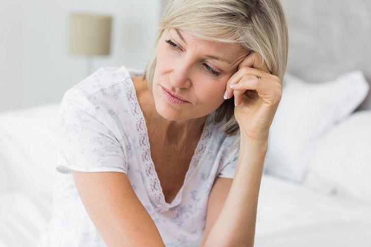 Reife Frau sitzt müde im Bett