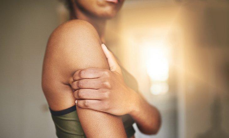 Frau hält sich den schmerzenden Arm