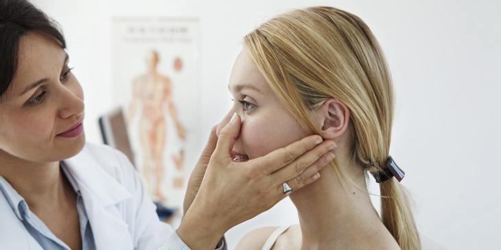 Ärztin drückt auf Wange