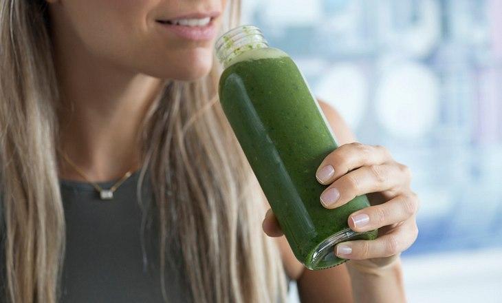 Frau trinkt grünen Smoothie