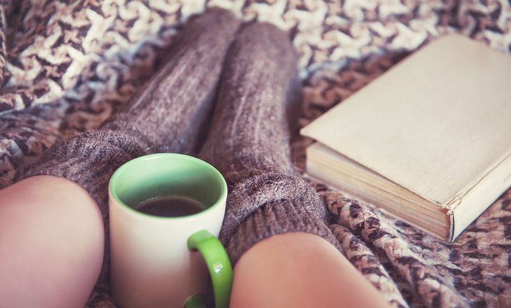 Frau trinkt Tee im Bett gegen Reizhusten