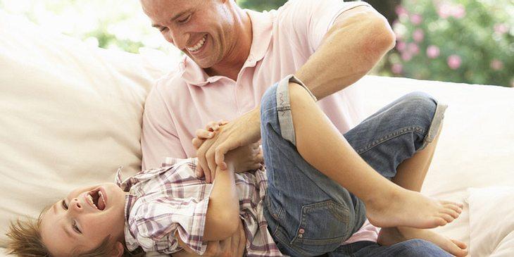 Ein Vater kitzelt seinen Sohn