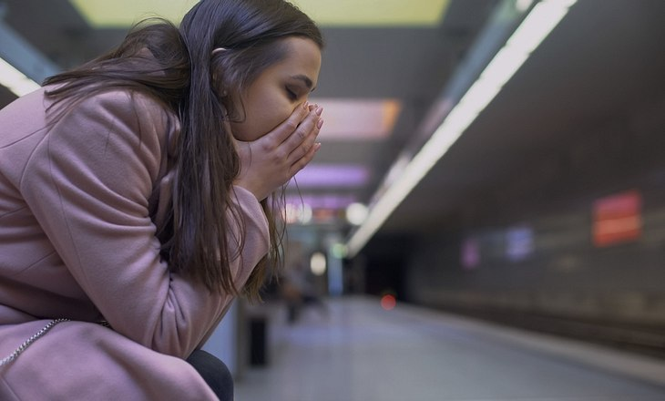 Frau sitzt verzweifelt in U-Bahn-Tunnel.